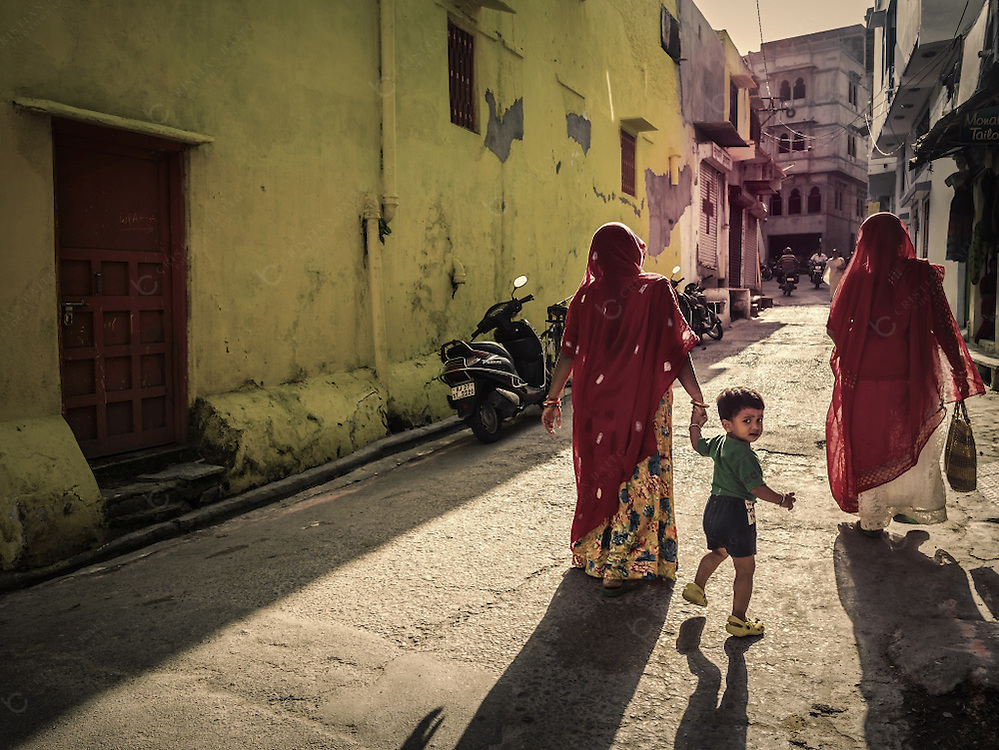 Woman with child among other people walking in the old quarter of Udaipur Rajasthan India. Udaipur was founded in in 1559 by Maharana Udai Singh. This city is a very popular tourist destination known by its many lakes, scenic locations, the Rajput palaces and culture.