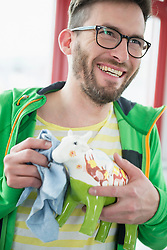 Young man cleaning cow ornament cloth smiling
