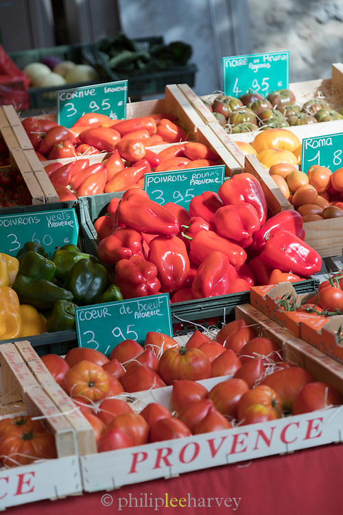 Choice of peppers and tomatoes in various colors on open-air market stall.