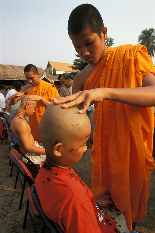 Shan boy gets his head shaved during Poy Sang Long, a ceremony att which boys are ordained as novice monks in Mae Hong Son, Thailand.