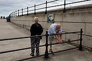 As his wife waits patiently on the seafront promenade, a middle-aged man stoops to attend a blister on his foot, on 14th July 2017, at Scarborough, North Yorkshire, England.