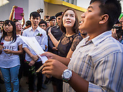 """14 FEBRUARY 2015 - BANGKOK, THAILAND: NATCHACAH KONG-UDOM, center, a Thai democracy advocate, and other protestors, participate in a chant during a protest against the military coup. Dozens of people gathered in front of the Bangkok Art and Culture Centre in Bangkok Saturday to hand out red roses and copies of George Orwell's """"1984."""" Protestors said they didn't support either Red Shirts or Yellow Shirts but wanted a return of democracy in Thailand. The protest was the largest protest since June 2014, against the military government of General Prayuth Chan-Ocha, who staged the coup against the elected government. Police made several arrests Saturday afternoon but the protest was not violent.    PHOTO BY JACK KURTZ"""