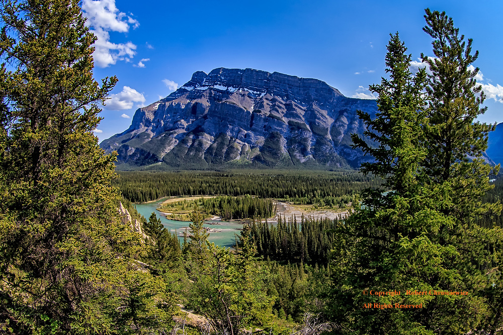 Bow River Valley: A dramatic view of the Bow River valley, with the imposing Mount Rundle 1 in the background, Banff National Park, Alberta Canada.
