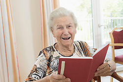 Portrait of happy senior woman reading book in rest home, Bavaria, Germany
