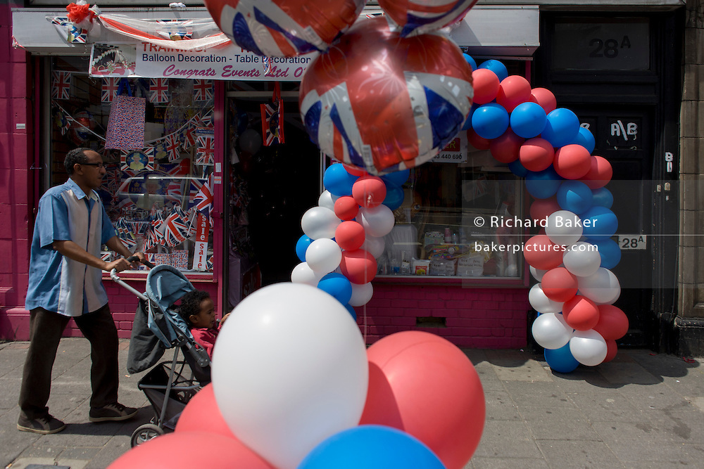 Father with child passing patriotic bunting, flags, balloons and royal memorabilia on display before the Queen's diamond Jubilee in a south London shop window.