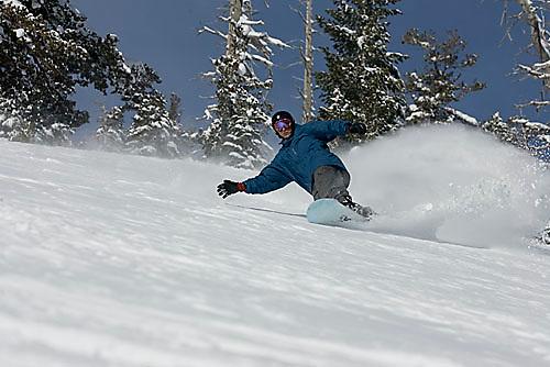 Young man snowboarding at Kirkwood ski resort near Lake Tahoe, CA.