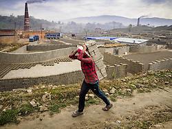 March 3, 2017 - Bagmati, Central Development Region, Nepal - Workers carry unbaked bricks from the fields where they're molded to a kiln for drying at a brick factory in Bagmati, near Bhaktapur. There are almost 50 brick factories in the valley near Bagmati. The brick makers are very busy making bricks for the reconstruction of Kathmandu, Bhaktapur and other cities in the Kathmandu valley that were badly damaged by the 2015 Nepal Earthquake. Most of the workers in the brick factories are migrant workers from southern Nepal. (Credit Image: © Jack Kurtz via ZUMA Wire)