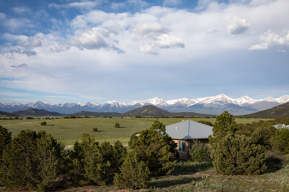 Spring after a wet winter turns the prairie green at Rancho Bendito, even as snow lingers in the Sangre de Cristo Range.