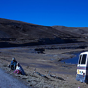 """Mountain Biking on Death Road, Bolivia...Locals watch A tour group of Mountain Bikers prepare at La Cumbre the starting point of the days ride along death road...The North Yugas Road is a 64 Kilometer road leading from La Paz to Corioico. It is legendary for it's extreme danger and in 1995 the Inter American Development Bank christened is as the """"world's most dangerous road"""".. The road was built in the 1930's during the Chaco War by Paraguayan prisoners to connect the Amazon rainforest region of Northern Bolivia to it's capital City La Paz. One estimate is that 200 to 300 travelers were killed yearly along the road. On 24 July 1983, a bus veered off the Yungas Road and into a canyon, killing more than 100 passengers in what is said to be Bolivia's worst road accident..A new stretch of the La Paz-Coroico highroad was opened in 2006 to bypass the notorious stretch known as death road..The danger of the road has now made it a popular tourist destination starting in the 1990's and drawing thrill-seekers and mountain bike enthusiasts who ride on the 64km mainly downhill stretch from La Cumbre, a 4,700 meter peak to Yolosa, a decent of 3600 meter's (11,800 feet). The journey includes breathtaking views of snow covered peaks and towering cliffs and starts along modern asphalted road before entering the jungle itself and the most dangerous and notorious part of the ride. The infamous narrow dirt road, most of the road no wider than 3.2meter's, is cut into the side of the mountain with sheer drops to the left of up to 600 meter's with virtually no safety rails on the winding steep decent..There are now many tour operators catering to this activity, providing information, guides, transport and equipment. Nevertheless, the Yungas Road remains dangerous. At least 13 of these cyclists died on the ride since 1998, the latest A 28-year-old Israeli traveler was killed in April 2010  the group of cyclists arrived at a heavily foggy area. The woman got separated from the group, and"""