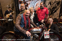 Andrea Radaelli (from Radikal Choppers) seated on the Radikal Choppers first place winner (in the EICMA Custom Show) with LowRide Magazine staff Danilo Seclì, Marie-Line Thioulouze, Giuseppe Roncen and Sara Jukic during EICMA, the largest international motorcycle exhibition in the world. Milan, Italy. November 21, 2015.  Photography ©2015 Michael Lichter.
