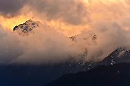 Alpenglo lit clouds swirl above Warrior Peak and Boulder Ridge at sunset, in Olympic National Forest, Olympic Mountains, as seen from the Kitsap Peninsula across Hood Canal in Puget Sound, Washington state, USA.