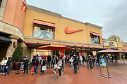 People stand in line outside the True Religion Brand Jeans, H&M and Nike stores the day before Christmas at the Citadel Outles amid the global coronavirus COVID-19 pandemic, Thursday, Dec. 24, 2020, in Los Angeles.