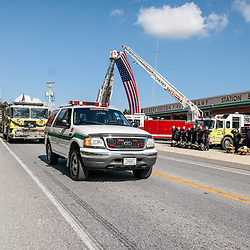 Peach Bottom, PA, USA - October 30, 2014: Fellow firefighters salute the funeral procession for a fallen volunteer firefighter st the Robert Fulton Fire Company in Lancaster County.