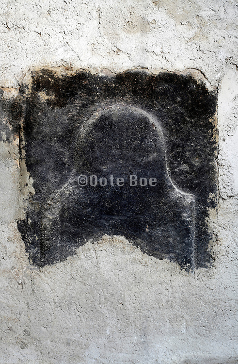 the blackened back wall plate of an open fireplace inside a house