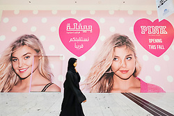 Woman walking past billboard for new Victoria's Secret shop in  City Centre shopping mall in Manama Kingdom of Bahrain