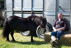© Licensed to London News Pictures.15/08/15<br /> Rosedale, UK. <br /> <br /> A man sits with his small pony during the Rosedale Country Show. This mainstay annual event remains as popular as ever attracting visitors and entrants from across the region.<br /> <br /> Photo credit : Ian Forsyth/LNP