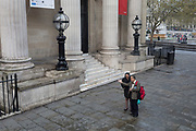 Pedestrians talk outside Canada House, in Trafalgar Square, Westminster on 9th April 2019, in London, England.