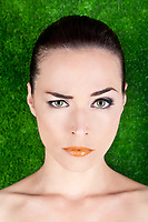 Closeup portrait of a serious beautiful woman raising an eyebrow on green background