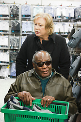 Volunteer carer helping visually-impaired wheelchair user to shop in supermarket, on a trip organised by a resource for people with physical and sensory impairment.