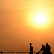 People walking by on the walkway on the banks of the Mekong River in Vientiane, Laos, are silhouetted against the low sun in a hazy sky turning the late afternoon sky a golden orange color.