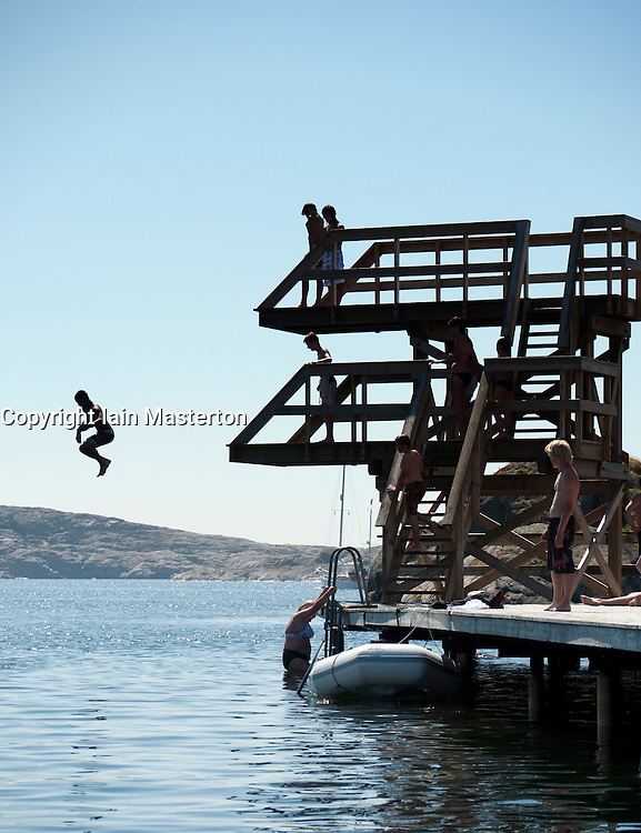 Children jumping from diving platforms into sea during summer at Skarhamn on Bohuslan coast in western Sweden