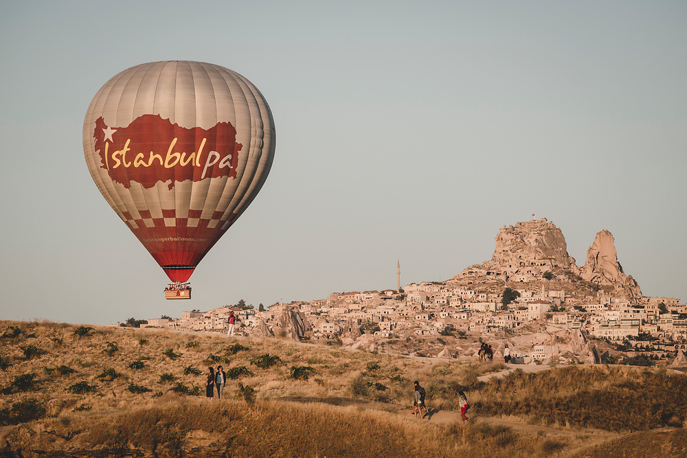 Göreme, Turkey - August 13, 2013: Tourists traveling in Turkey walk at sunrise on a hillside as a hot air balloon passes by in the Cappadocian town of Göreme.