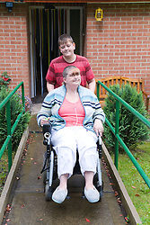 Young carer pushing his mother; who is severely asthmatic; in a wheel chair down a ramp outside their house,