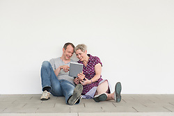 Mature couple using digital tablet, smiling