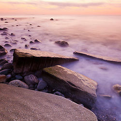 Pre-dawn light and waves wash over the rocks at Rye Harbor State Park in Rye, New Hampshire.