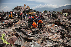 October 4, 2018 - Palu, Central Sulawesi, Indonesia - Indonesian rescuer and search carry the body bag of victim during evacuation at Balaroa village, in Palu on 4 October 2018, Central Sulawesi, Indonesia. Life is hold for living in tents and shelters in the Indonesian city hit by a powerful earthquake and tsunami, unsure when they'll be able to rebuild and spending hours each day often futilely trying to secure necessities such as fuel for generators. A total of 1,411 people have been confirmed dead and over 2,500 injured after the monster earthquake struck on September 28 sending destructive waves barrelling into Sulawesi island. (Credit Image: © Ivan Damanik/ZUMA Wire)