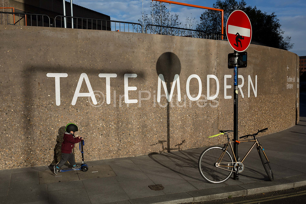 A young boy on his mini scooter passes the Tate Modern art gallery on the Southbank, on 13th November 2017, in London, England.