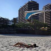 A hang glider lands on the beach as a sunbather lies in the late afternoon light at Sao Conrado beach, Rio de Janeiro,  Brazil. 8th July 2010. Photo Tim Clayton...