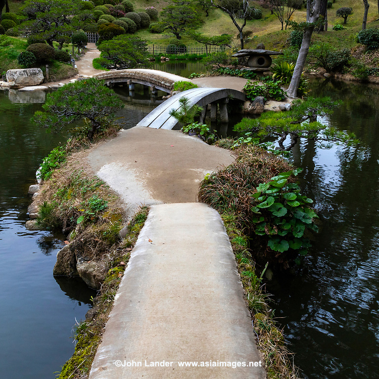 Zig Zag Bridge at Shukkeien Garden - Shukkeien garden was built in 1620 by Ueda Soko - a warrior who became a Buddhist monk, tea master and landscape gardener.  It was designed and built for the villa of Asano Nagaakira, daimyo of Hiroshima.  Shukkeien distorts concepts of space, cramming a miniaturized version of the landscape of West Lake Hangzhou China into a space of just 40,000 square meters.  Even its name means shrunken-scenery garden. Shukkeien contains many of the elements of classic landscape gardens introduced from China by Zen priest Muso Kokushi: evocatively shaped rocks, pavilions and a large pond with small islands. Around Takuei Pond with its hump-backed Rainbow Bridge winding paths lead visitors through miniature mountains, valleys, fields and groves.  Shukkeien's Seifukan teahouse, with its thatched roof and lyre-shaped window, a different tea ceremony is held each month to celebrate the flowers of each successive season.