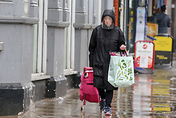 © Licensed to London News Pictures. 14/09/2021. London, UK. A woman wearing a shield during rainfall in north London. A yellow weather warning for heavy rain is in place in London and parts of South East England. Photo credit: Dinendra Haria/LNP