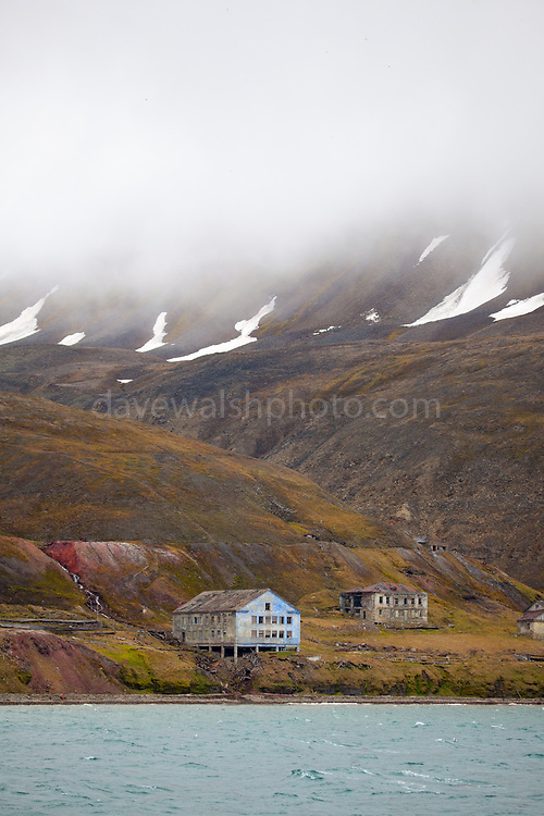 """Remains of 20th century coal mining on the coast of Isjforden, Svalbard. The cliffs are marked with the signs of coal mining from the 20th century, and covered green tundra vegettion that grows during the short summer season - which is lengthening due to climate change. This mage can be licensed via Millennium Images. Contact me for more details, or email mail@milim.com For prints, contact me, or click """"add to cart"""" to some standard print options."""