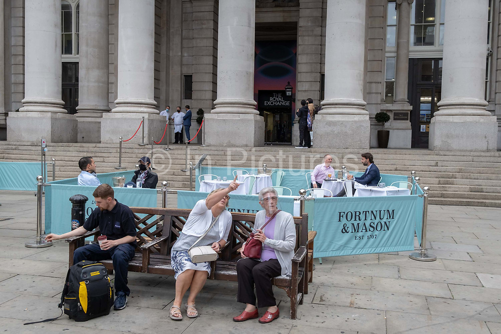 Two ladies sit in front of diners and drinkers who are within street barriers where Fortnum & Masons have set up an outdoor restaurant and bar in front of the Royal Exchange at Bank, in the City of London, during the Coronavirus pandemic, on 9th September 2020, in London, England.