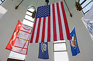 East Meadow, New York, USA. May 25, 2019. The American Flag and military flags of the United States Armed Forces - Army, Navy, Marine Corps, Air Force, Coast Guard - are suspended in the high ceiling of The Veterans Memorial building, open for visitors during Saturday of Memorial Day Weekend at Eisenhower Park on Long Island.
