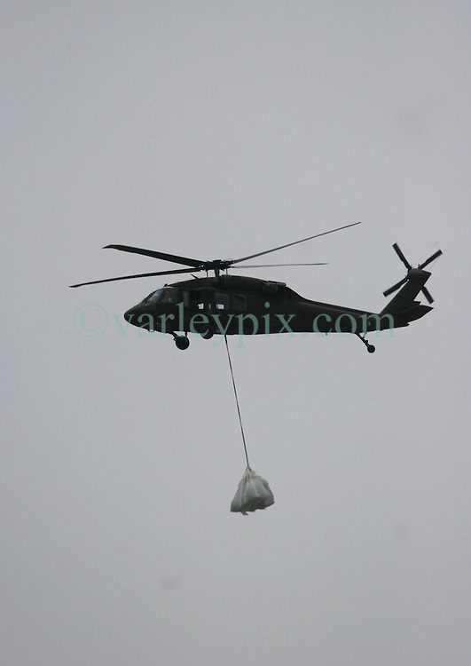 13 May 2010. Elmer Island, Lafourche Parish, Louisiana. <br /> A Louisiana National Guard helicopter ferrying sand bags works with the 922nd Horizontal Engineer Company, 769th Engineer Battalion fight a losing battle against mother nature as they battle against the strong currents to close the inland waterways from the ocean now depositing oil from the Deepwater Horizon catastrophe on the beaches. <br /> Photo credit;Charlie Varley/varleypix.com