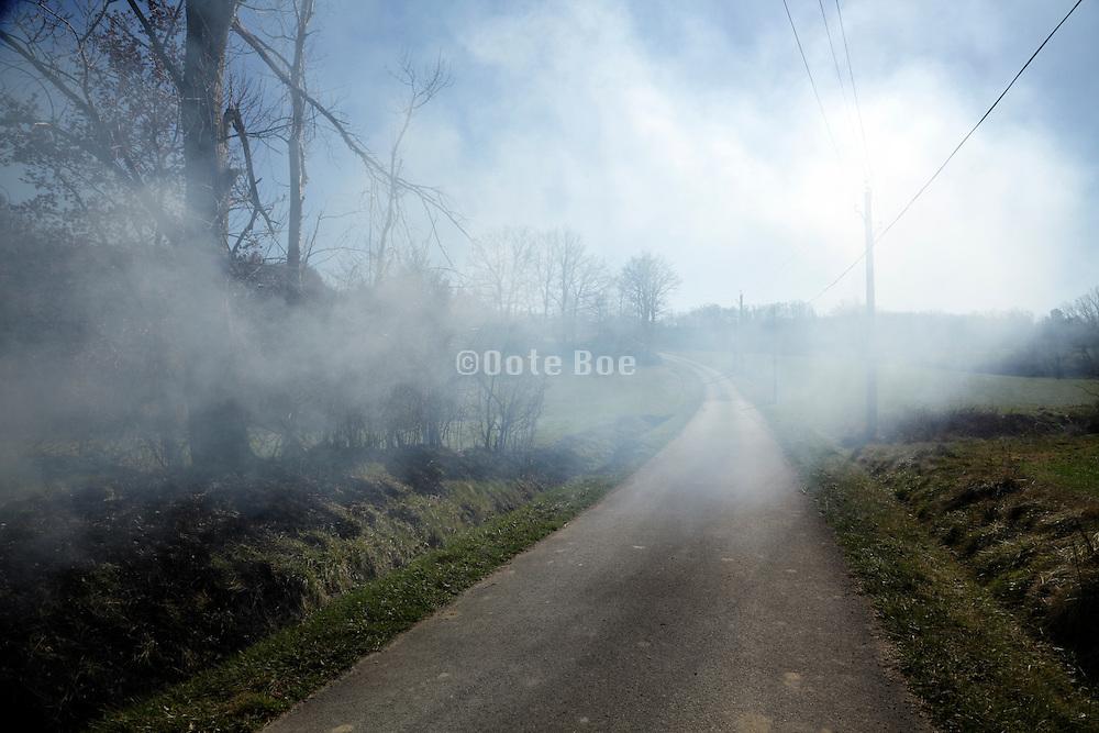 smoke from a roadside burn hanging over rural landscape