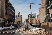 Two people walking on the crossroad on Husdon Street and Gansevoort Street intersection, New York City, New York, United States of America. The streets have mounds of snow on the side where they have been cleared after the record breaking snowstorm in January 2016.  (photo by Andrew Aitchison / In pictures via Getty Images)
