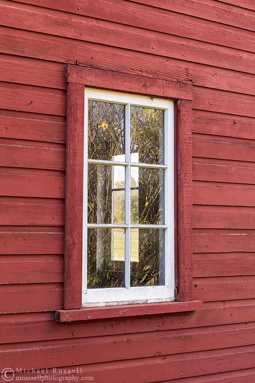 Fall foliage is reflected on a window of the red Gambrel Roof Barn (built in 1939) on Len Rowlatt's farmland in Langley.  This farmland was first used by Joseph and Sarah Anne Annand and later by Len Rowlatt until his death in 1972.  The property is now part of Campbell Valley Regional Park in Langley, British Columbia, Canada.