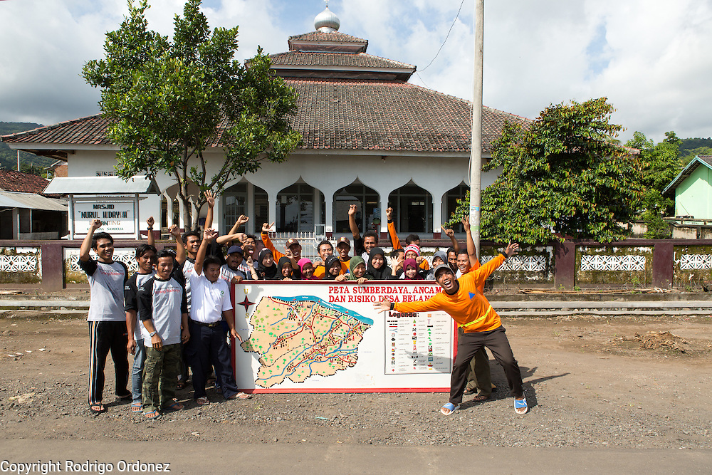 Members of the emergency preparedness team in Belanting pose for photograph with a large map showing the village's risks, emergency meeting points and evacuation routes. Belanting is located in Sambelia district, East Lombok, West Nusa Tenggara province, Indonesia.