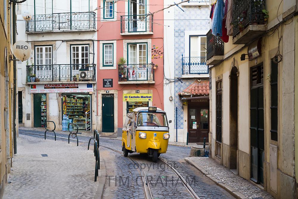 Piaggio Ape tuk tuk type three-wheeler passenger vehicle and tram tracks, narrow steep shopping street in Alfama District, Lisbon, Portugal