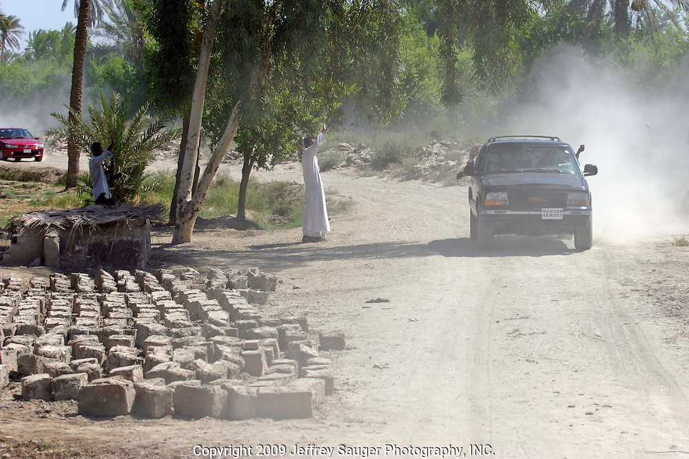 Malik Al-kasid's truck leads a caravan of relatives as many villagers along the way turned out to welcome him home on the way to Al-kasid's Istikbal, or homecoming, in his home village Suq ash Shuyukh on the outskirts of Nasiriyah, Iraq, Tuesday, July 29, 2003. Al-kasid is seated at left. Mud bricks, made by hand, for building a home are at left. The Al-kasid family fled Iraq after the Gulf War and their part in the uprising against Saddam Hussein in 1991, spent 3 years in Rafa, Saudi Arabia and finally settled in Dearborn, MI.The family hasn't been home to Iraq in 13 years.
