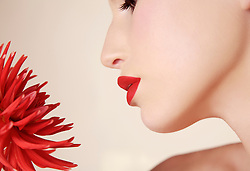Extreme close up of young beautiful woman inhaling red dahlia