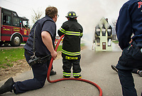 Laconia Fire's Chad Vaillancourt assists Paul Swenson as he puts out his first fire shortly after being sworm in as an honorary member of the department on Sunday during Swenson's Make A Wish day.  (Karen Bobotas/for the Laconia Daily Sun)