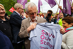 "© Licensed to London News Pictures. 25/05/2016. London, UK. Leader of opposition and Labour leader JEREMY CORBYN is given a ""Save Our Steel"" t-shirt by a steel worker whilst joining hundreds of steelworkers from across the UK to march through Westminster in London to keep up pressure for government help for steel industry on Wednesday, 25 May 2016. Photo credit: Tolga Akmen/LNP"