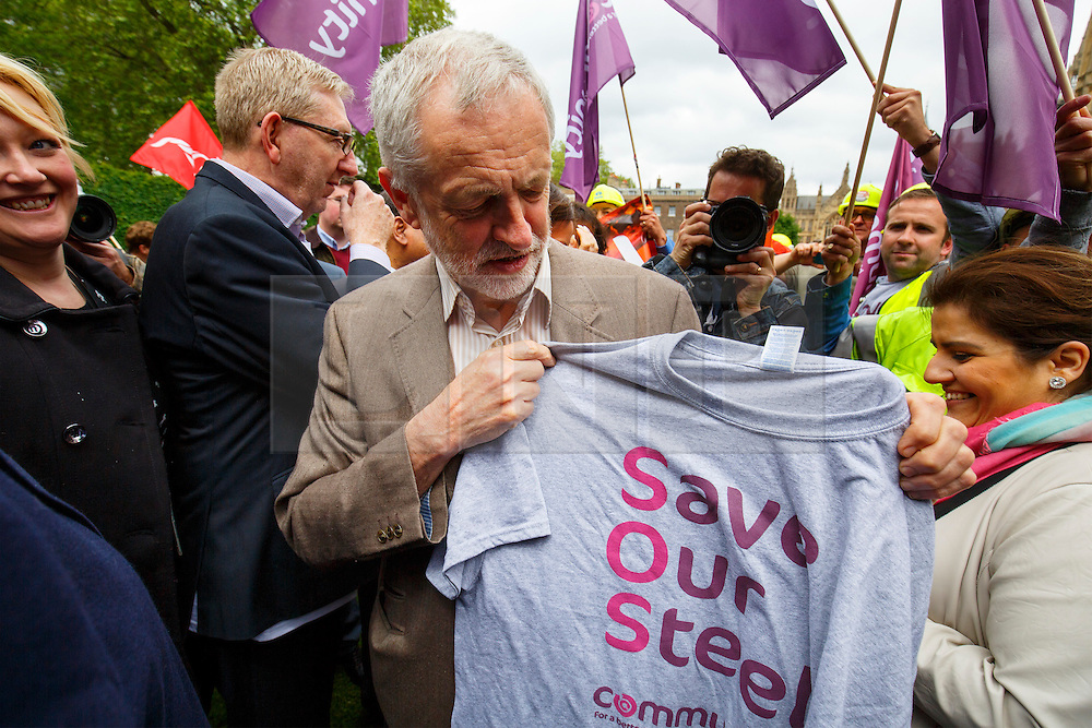 """© Licensed to London News Pictures. 25/05/2016. London, UK. Leader of opposition and Labour leader JEREMY CORBYN is given a """"Save Our Steel"""" t-shirt by a steel worker whilst joining hundreds of steelworkers from across the UK to march through Westminster in London to keep up pressure for government help for steel industry on Wednesday, 25 May 2016. Photo credit: Tolga Akmen/LNP"""
