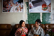 Two japanese students in their kimonos drinking beer in a bar in the Mitte, Berlin, Germany