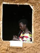 Kigali, Rwanda -A Rwandan woman works on a traditional basket by the light of an open window at a church in a rural area near Kigali, Rwanda.
